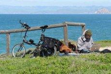Turysta podczas podróży ładuje laptopa za pomocą przenośnych baterii słonecznych.
