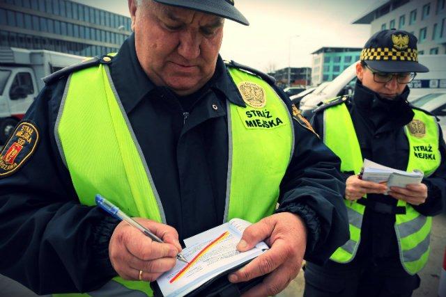 Starszy Inspektor Anna Pietrzak i starszy inspektor Krzysztof Rolek wypisują mandaty za złe parkowanie samochodu .